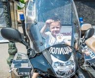 El muchacho se está sentando en una motocicleta de la policía el día de la policía marcado en Novi Sad fotos de archivo libres de regalías