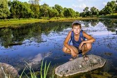 El muchacho se está sentando en una roca por el lago Fotografía de archivo