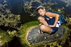 El muchacho se está sentando en una roca por el lago Imagen de archivo libre de regalías