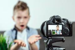 El muchacho se est? sentando delante de una c?mara de SLR, primer Blogger, blogueando, tecnolog?a, ganancias en Internet Copie el fotografía de archivo libre de regalías