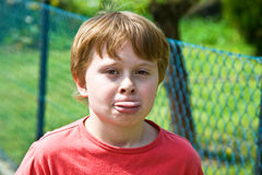 El muchacho se pega hacia fuera la lengua y pega una actitud divertida Imagen de archivo libre de regalías
