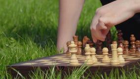 El muchacho se prepara al juego de ajedrez y puso las figuras en el tablero de ajedrez almacen de video