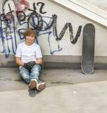 El muchacho se relaja con su tablero del patín en el parque del patín Fotos de archivo libres de regalías