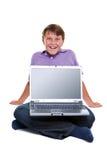 El muchacho se sentó con la computadora portátil en su pantalla en blanco de las piernas Fotografía de archivo libre de regalías
