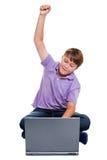 El muchacho se sentó con la computadora portátil que perforaba el aire aislado Imagen de archivo libre de regalías