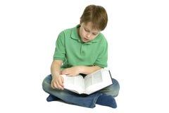El muchacho se sentó leyendo un libro. Foto de archivo libre de regalías