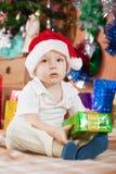 El muchacho se sienta con el regalo de la Navidad Foto de archivo