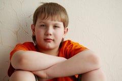 El muchacho se sienta con el suyo de nuevo a la pared Imagen de archivo