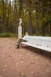 El muchacho se sienta en banco en parque del otoño Foto de archivo libre de regalías