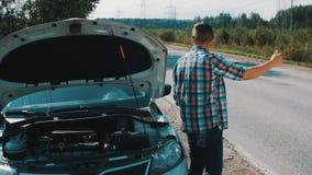 El muchacho se sienta en el coche quebrado en el camino hitchhiking Para ayuda que espera Pulgar para arriba Verano almacen de video
