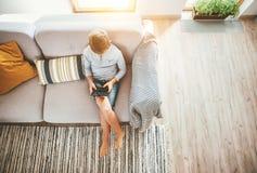 El muchacho se sienta en juegos del sofá con la opinión superior de la cámara del smartphone y del gamepad Concepto del niño y de foto de archivo libre de regalías