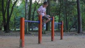 El muchacho se sienta en la barra y los saltos de él almacen de video