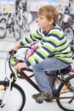 El muchacho se sienta en la bicicleta y mira en distancia Imágenes de archivo libres de regalías
