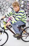 El muchacho se sienta en la bicicleta y mira la cámara Imagen de archivo
