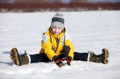 El muchacho se sienta en la nieve Imagen de archivo libre de regalías