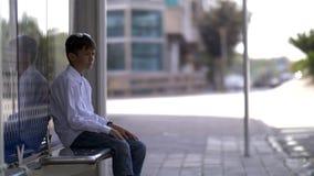 El muchacho se sienta en la parada y las esperas de autobús para el autobús imagenes de archivo