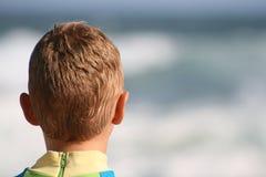 El muchacho se sienta en la playa Fotos de archivo libres de regalías
