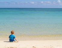 El muchacho se sienta en la playa imagen de archivo