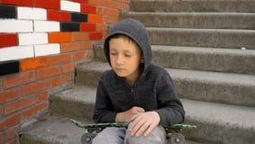 El muchacho se sienta en los pasos y sostiene un monopat?n en sus manos almacen de video
