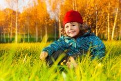 El muchacho se sienta en parque del otoño Imagen de archivo