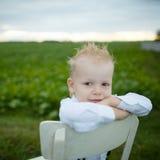 El muchacho se sienta en silla en el campo Imagen de archivo libre de regalías