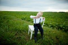 El muchacho se sienta en silla en el campo Foto de archivo