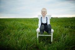 El muchacho se sienta en silla en el campo Imágenes de archivo libres de regalías