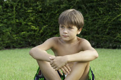 El muchacho se sienta en un césped Fotos de archivo