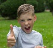 El muchacho se sienta en un césped verde y aumenta un finger para arriba fotografía de archivo libre de regalías