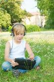El muchacho se sienta en un parque con una tableta digital Fotografía de archivo libre de regalías
