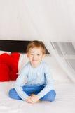 El muchacho se sienta en una cama en una situación cómoda Fotos de archivo libres de regalías
