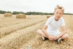 El muchacho se sienta solamente en campo de trigo cosechado Foto de archivo