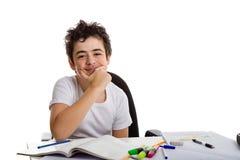 El muchacho se sostiene la barbilla que sonríe delante de la preparación Imagen de archivo libre de regalías