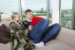 El muchacho se vistió en el traje del dinosaurio que se sentaba con el libro de la historia de la lectura del padre en sofá cama e Fotografía de archivo
