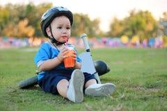 El muchacho sentó y bebió el agua en el césped al lado de la bici fotografía de archivo libre de regalías