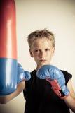 El muchacho serio pega el saco de arena con los guantes azules Fotografía de archivo libre de regalías