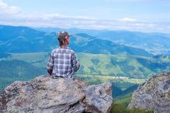 El muchacho sienta en el acantilado en frente las montañas Foto de archivo libre de regalías