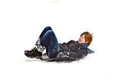 El muchacho sledging abajo de la colina en paisaje hivernal Fotografía de archivo libre de regalías