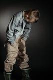 El muchacho solo mira fijamente su ropa de gran tamaño Foto de archivo