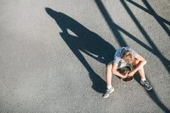 El muchacho solo sin los amigos se sienta en el monopatín Soledad c del niño Imagen de archivo libre de regalías