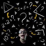 El muchacho soluciona ejemplos de las matemáticas en la pizarra imágenes de archivo libres de regalías