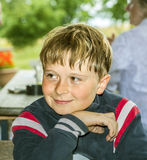 El muchacho sonríe y se divierte que se sienta en la tabla Imagen de archivo