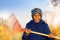 El muchacho sonriente africano sostiene el rastrillo rojo con emociones Fotografía de archivo