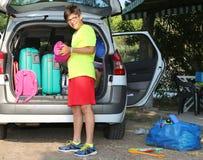 El muchacho sonriente carga bolsos en el coche de equipaje Fotos de archivo