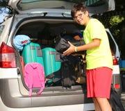 El muchacho sonriente carga bolsos en el coche de equipaje Fotografía de archivo libre de regalías