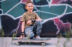 El muchacho sonriente con el monopatín se sienta cerca de la pared pintada grafity Imágenes de archivo libres de regalías