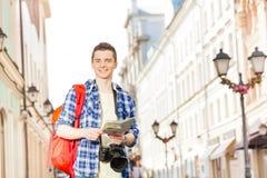 El muchacho sonriente con la cámara y la ciudad trazan en la calle Foto de archivo