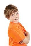 El muchacho sonriente con los brazos plegables se coloca mitad-dado vuelta Imagenes de archivo
