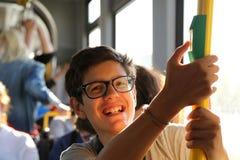 El muchacho sonriente con los vidrios elegantes viaja en tranvía Imagenes de archivo