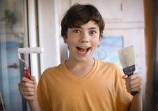 El muchacho sonriente del adolescente con el rodillo de pintura blanco y la cara sucia hacen para repintar Imagen de archivo libre de regalías